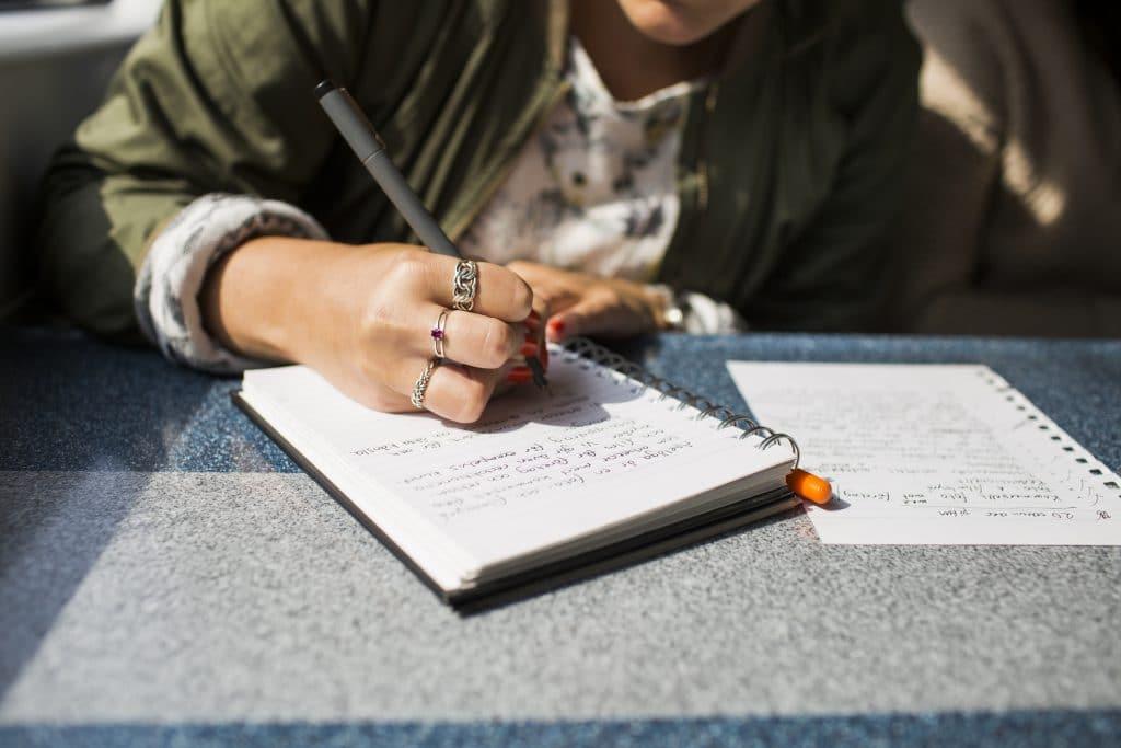 Femme qui écrit sur une feuille blanche