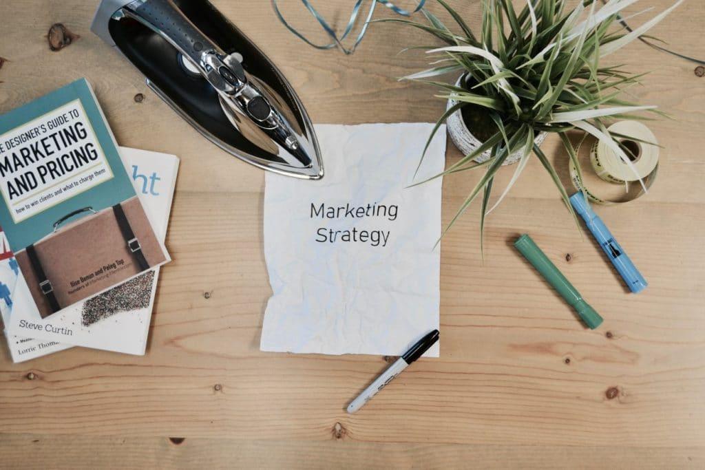 bureau avec une feuille sur laquelle il est écrit stratégie marketing